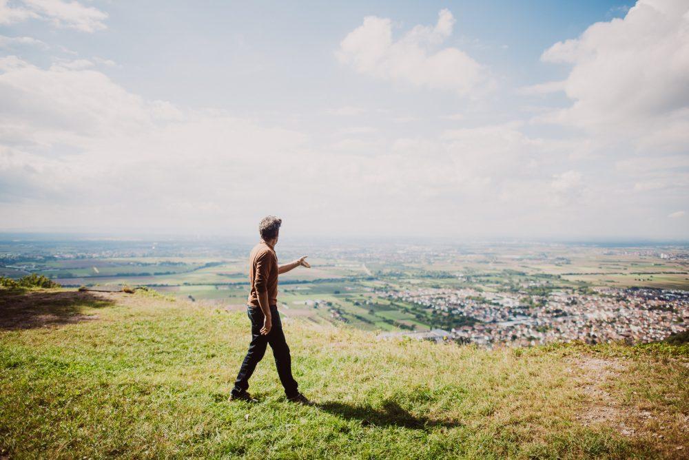 Ausblick auf weiten Horizont, Mann steht auf Wiese in Vordergrund