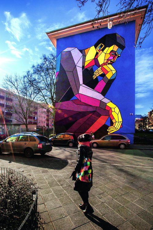 Hauswand mit Graffiti mit knieendem Mann in knalligen Farben